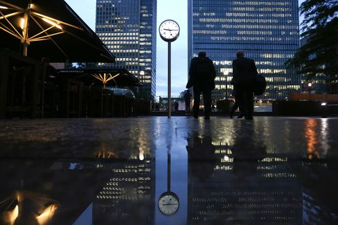 Commuters walk past buildings illuminated at night in the Canary Wharf business, financial and shopping district of London, U.K., on Oct. 28, 2015.