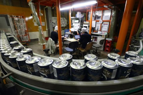 Cans of Indo no Aooni craft beer move along a conveyor on the production line of the Yo-Ho Brewing Co. brewery in Saku, Nagano Prefecture, on March 20, 2015. Photographer: Tomohiro Ohsumi/Bloomberg