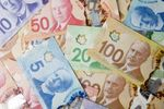 Canadian dollar banknotes are displayed in an arranged photograph.