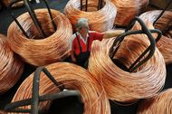 A worker inspects coiled bundles of 8mm copper wire before shipping in a warehouse at the copper mining and smelting complex, operated by RTB Bor Group, in Bor, Serbia, on Friday, Aug. 24, 2012. Copper neared a one-week low in London on signs Asian economies are slowing and speculation that U.S. policy makers will refrain from a fresh round of stimulus. Photographer: Oliver Bunic/Bloomberg