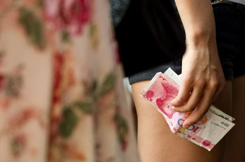 A tourist holds 100 yuan bank notes in Beijing, China.