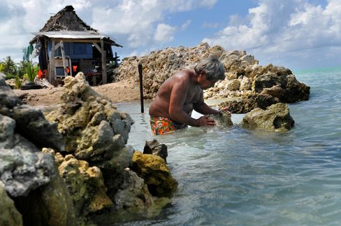 A man rebuilds his sea wall to protect his home in the village of Abarao on the island of Tarawa.