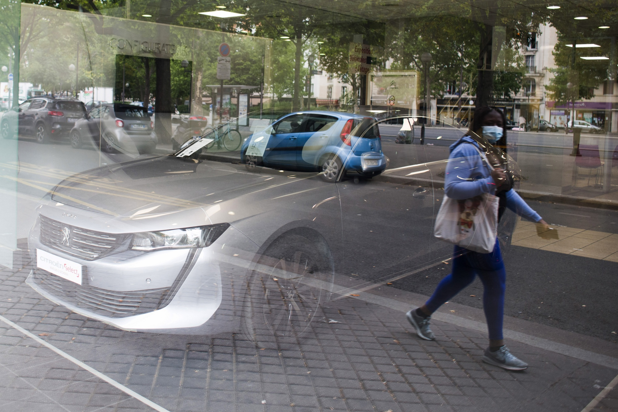 A pedestrian wearing a protective face mask is reflected in the window of the Citroen Nation automobile showroom, in Paris.