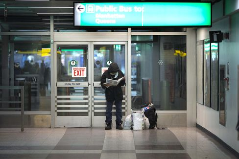 A homeless man reads a newspaper in Terminal B of LaGuardia Airport.