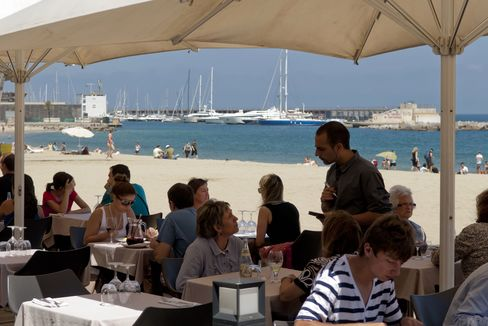 A Waiter Serves Customers at a Beach Bar in Barcelona