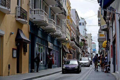 Pedestrians walk along Calle Fortaleza in Old San Juan, Puerto Rico, on Aug. 14.
