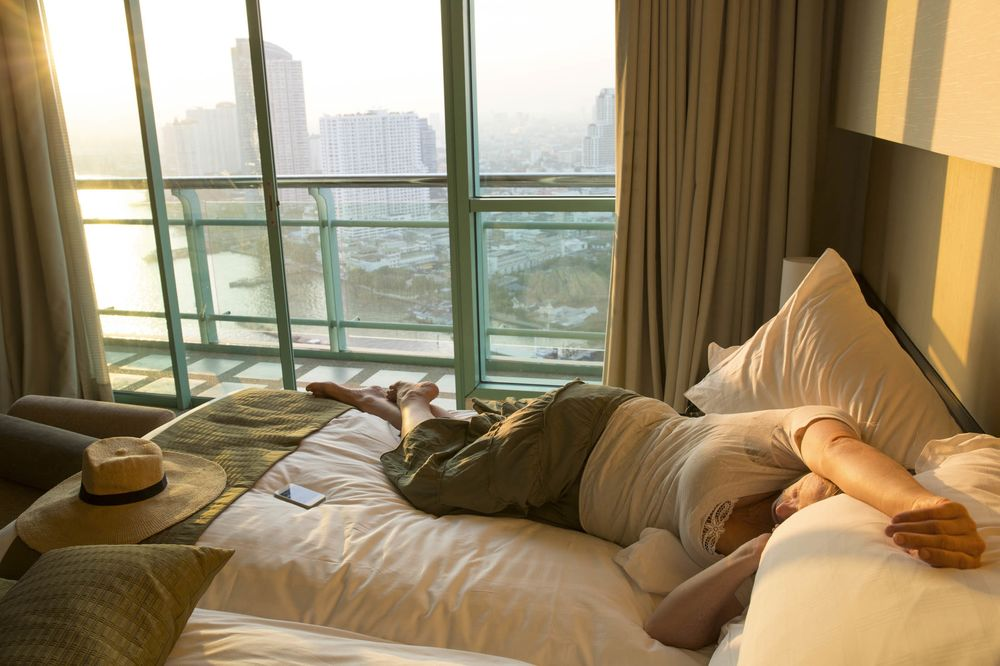 Woman relaxes in hotel room, asleep on bed,city behind