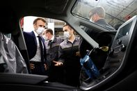 Emmanuel Macron listens to a Renault worker talking about an electric car during his visit in Douai, France, on June 28.