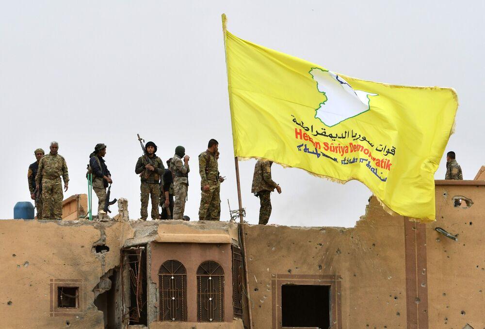 Les combattants des Forces démocratiques syriennes se tiennent au sommet d'un toit à côté de leur drapeau déployé à Baghouz, dans la province de Deir Ezzor, dans l'est de la Syrie.