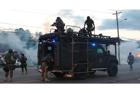 Tactical officers fire tear gas on Aug. 11 in Ferguson, Mo.