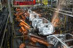 Robotic machines weld together the frames of vehicles during production at the General Motors Co. assembly plant in Arlington, Texas.