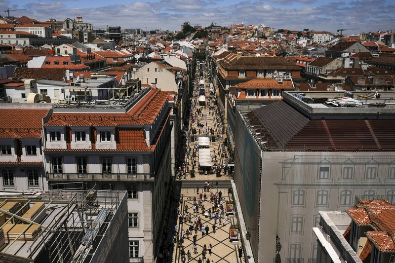 Pedestrians walk along Augusta street in the Baixa district of Lisbon, Portugal.