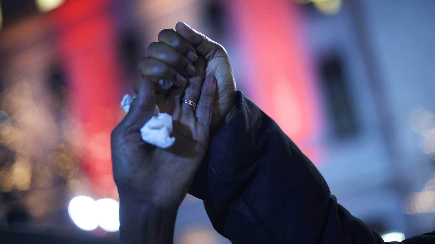 Demonstrators clutch hands while gathering in Philadelphia to protest the grand jury decision during a Christmas Tree lighting ceremony at City Hall on Dec. 3, 2014.