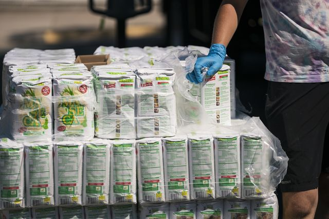 A volunteer distributes corn masa flour to local residents during a pop-up grocery event at Powderhorn Park in Minneapolis, Minnesota on July 24, 2020.
