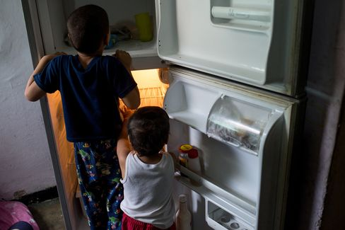Boys play with the refrigerator at their home in Catia.