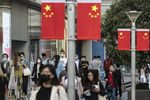 Morning commuters wearing protective masks walk past Chinese flags displayed along Nanjing Road in Shanghai, China, on Friday,