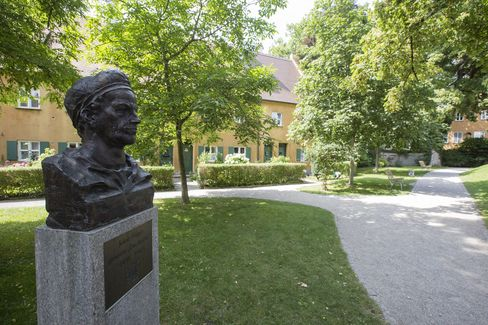 A bronze bust of Jakob Fugger, founder of the Fuggerei social housing complex, stands in a communal garden area in Augsburg, Germany.