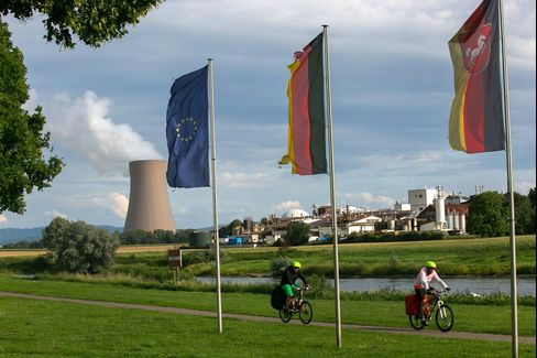 Cyclists ride beneath flags as Grohnde nuclear power plant stands beyond in July 2015.