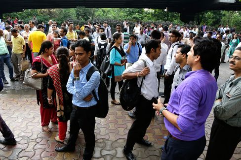 People stand outdoors after they rushed out of their offices following tremors in Kolkata, India, on Wednesday, Aug. 24, 2016. Officials say a powerful earthquake measuring a preliminary magnitude of 6.8 has shaken central Myanmar.