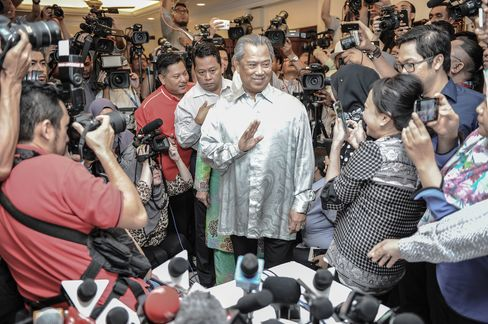 Muhyiddin Yassin waves to journalists as he arrives before a press conference a day after he was ousted as Malaysia's Deputy Prime Minister.