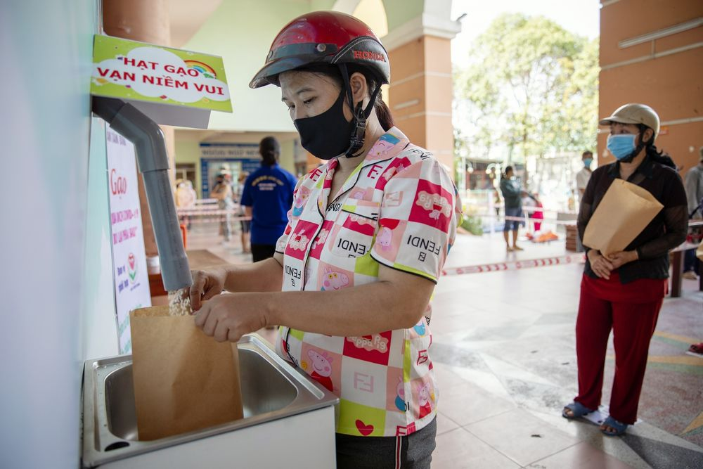 A woman receives rice from a 'rice ATM' in the Tan Binh district of Ho Chi Minh City, April 22. Photographer: Maika Elan/Bloomberg