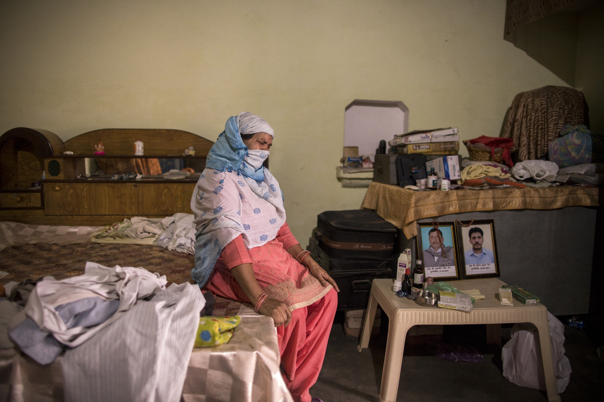 Wife of Covid fatality Kuwarsen Singh weeps next to portraits of diseased Kuwarsen Singh (L) and his son Pravinder Kumar. Kuwarsen singh was sent to an election duty where he was infected with the Covid virus. Picture taken at his house in the village Bassi, in Baghpath, Uttar Pradesh, India
