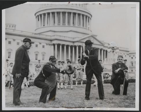 On an April afternoon in 1938, even the House's leadership had spring fever. Speaker William Bankhead took up the bat, with Majority Leader Sam Rayburn catching and Minority Leader Bertrand Snell serving as umpire. The House Pages, likely interrupted in their own game, made a backdrop for the photo op.
