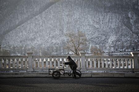 A man pushes a bicycle rickshaw.