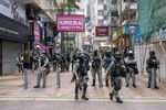 Riot police stand in front of closed stores in the Causeway Bay district during a protest in Hong Kong, China, on Wednesday, May 27, 2020.
