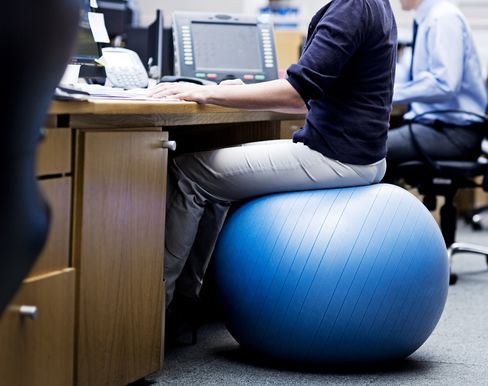 Woman in office sitting on an exercise ball | location: Cape Town, South Africa | description: Woman in office sitting on an exercise ball | location: Cape Town, South Africa