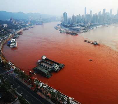 Aerial view of a ship motoring across the junction of the red-colored Yangtze River (left) and the Jialin River on September 6, 2012 in Chongqing, China.