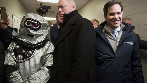A security guard stands between Senator Marco Rubio and a man dressed as a robot during a visit to a polling station in Bedford, New Hampshire, on Feb. 9, 2016.