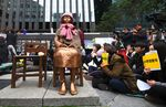 "South Korean protesters sit near a statue of a teenage girl symbolizing former ""comfort women"", who served as sex slaves for Japanese soldiers during World War II, during a weekly anti-Japanese demonstration."