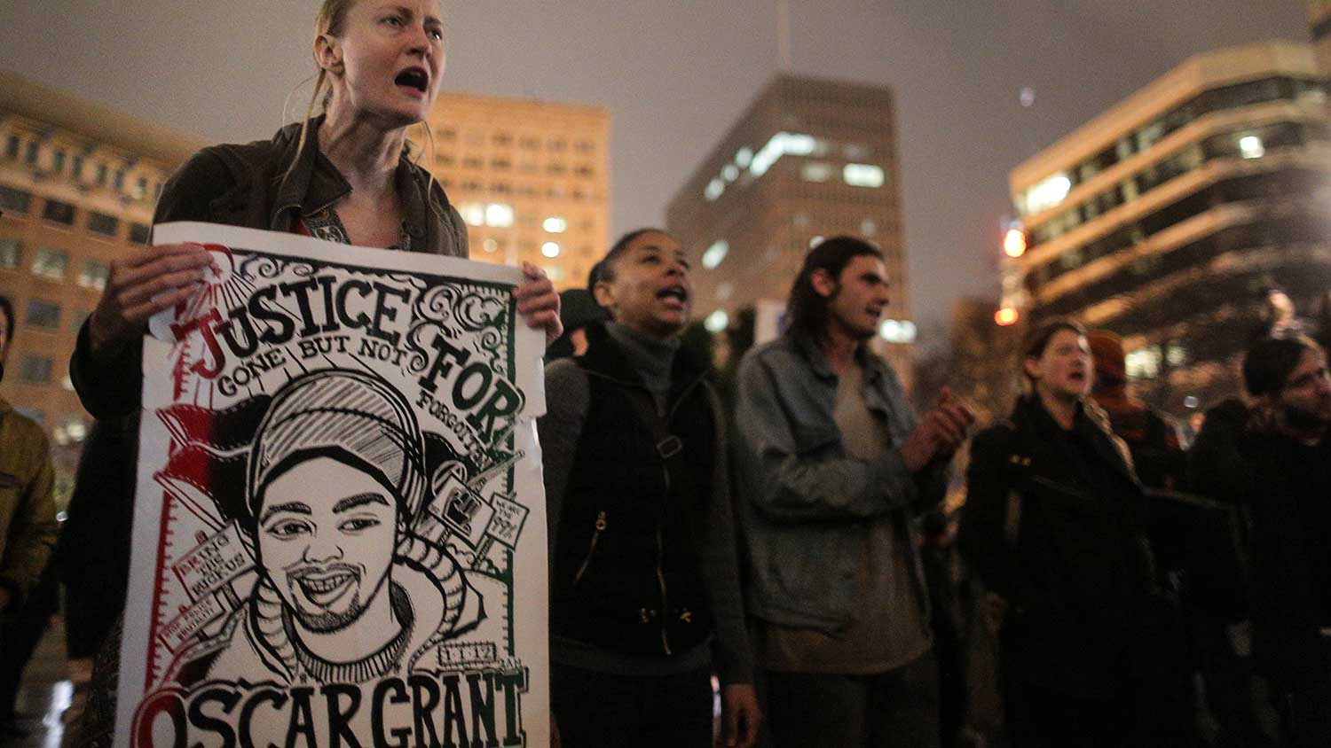 "Jessica Long of San Francisco holds a ""Justice for Oscar Grant"" poster during a demonstration following the grand jury's decision on Dec. 3, 2014, in Oakland, Calif."