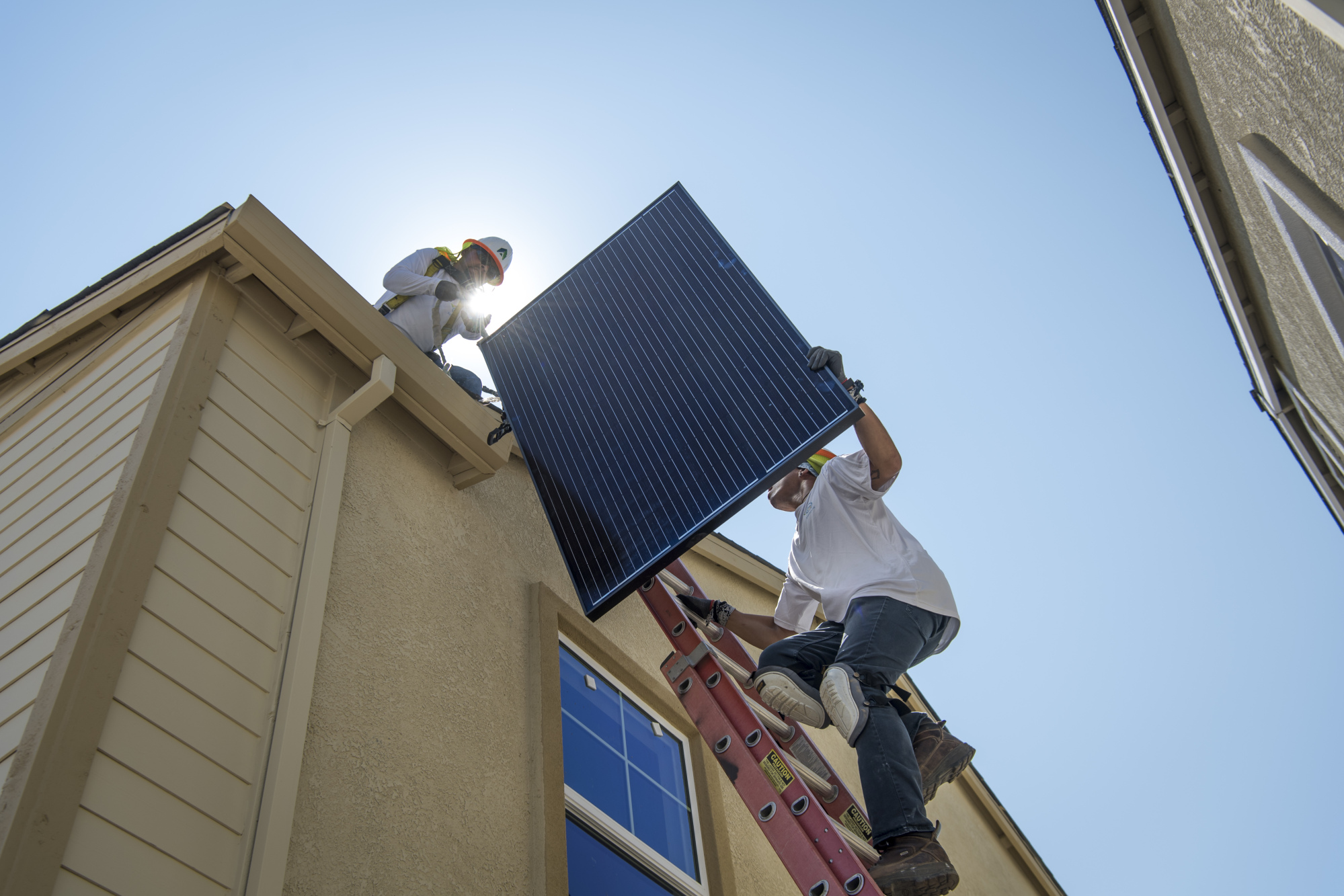 Contractors move a Sunrun Inc. solar panel up to the roof of a new home in Sacramento, California.
