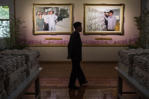 Portraits of Kim Il-Sung, left, and Kim Jong-Il at a silk factory.