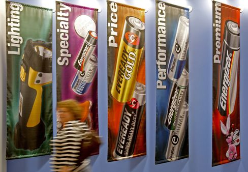 A Woman Walks Past Banners Displaying Energizer Batteries