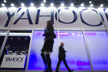 Pedestrians pass the Yahoo Inc. pavilion on day two of the Mobile World Congress in Barcelona, Spain, on Tuesday, Feb. 25, 2014.