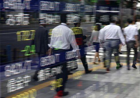 株価ボードと歩行者