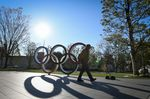 A pedestrian walks past the Olympics rings in Tokyo, Japan.