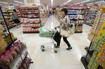 A customer pushes a shopping cart at an Aeon Co. supermarket during a sale jointly held with Daiei Inc. in Tokyo, Japan, on Thursday, Aug. 22, 2013. Aeon's acquisition of 48.4 million Daiei shares will take place on Aug. 27 after the completion of tender offer yesterday, according to a statement to the Tokyo Stock Exchange released today.