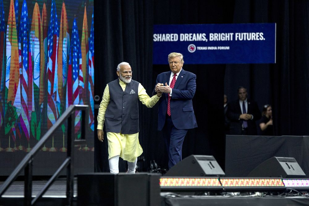 Narendra Modi and Donald Trump walk on stage together during the Howdy Modi Community Summit in Houston, Texas, on Sunday.