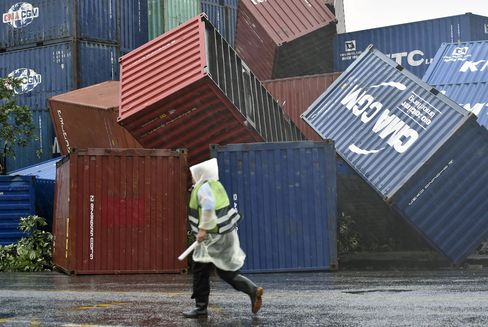 A man walks past downed shipping containers at the Kaohsiung Harbour in Taiwan.