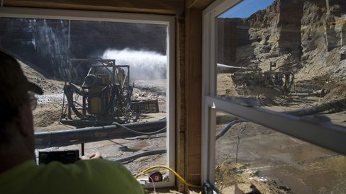 A worker controls water spray for hydraulic mining inside a mine operated by Superior Silica Sands in Wisconsin.