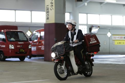 A mail carrier departs from a Japan Post post office