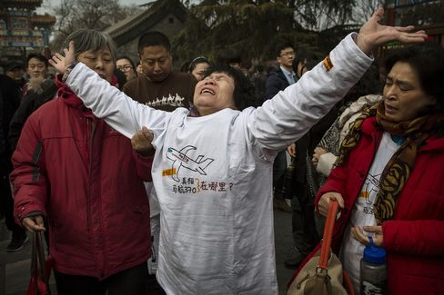A Chinese relative of a missing passenger on Malaysia Airlines flight MH370 reacts outside the main gate of the Lama Temple in Beijing, China.