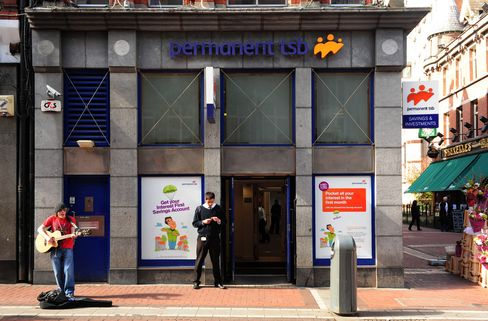 A Busker Stands Outside a Branch of the Permanent TSB in Dublin