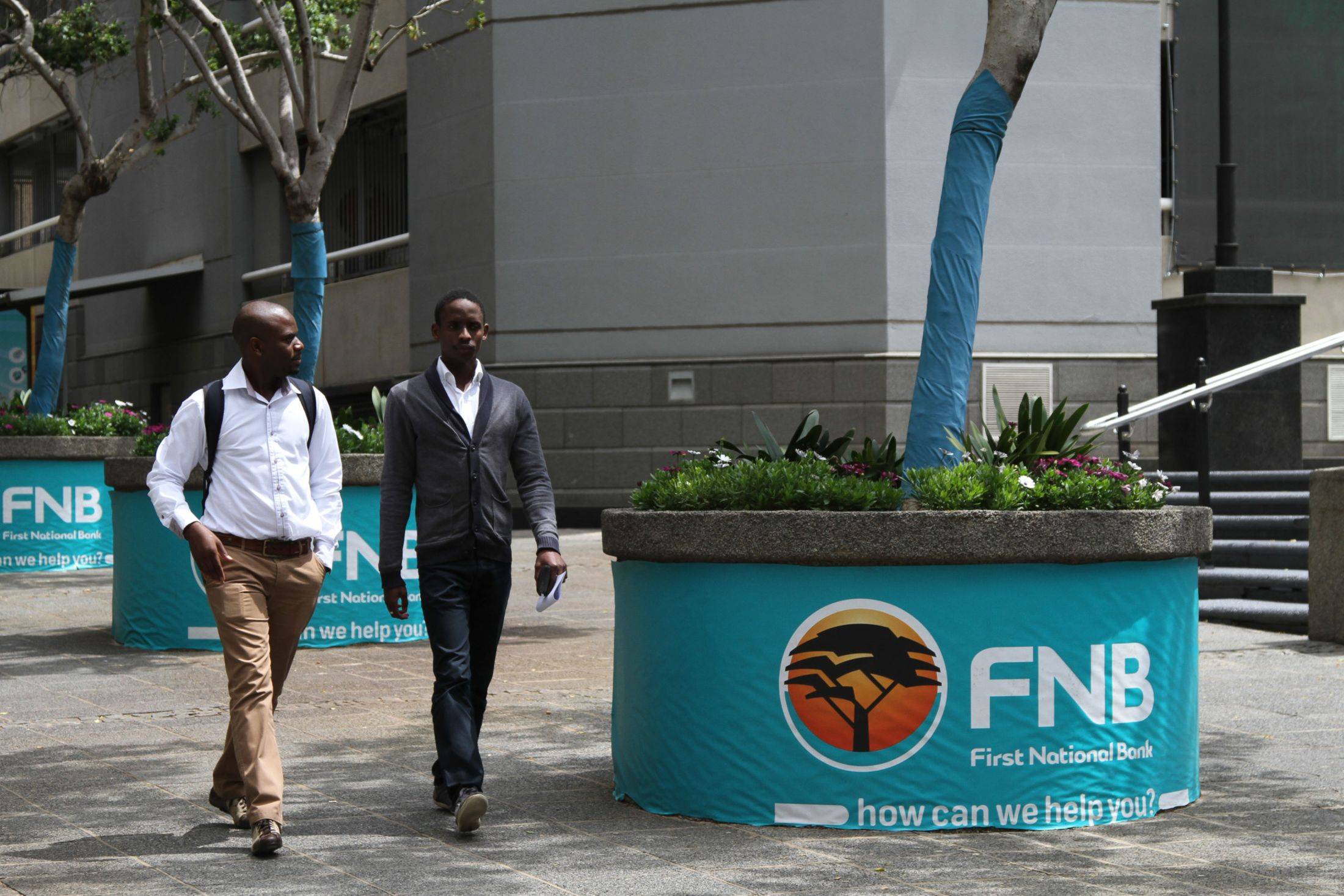 Pedestrians pass street advertising for First National Bank (FNB), a division of FirstRand Bank Ltd., in Johannesburg.