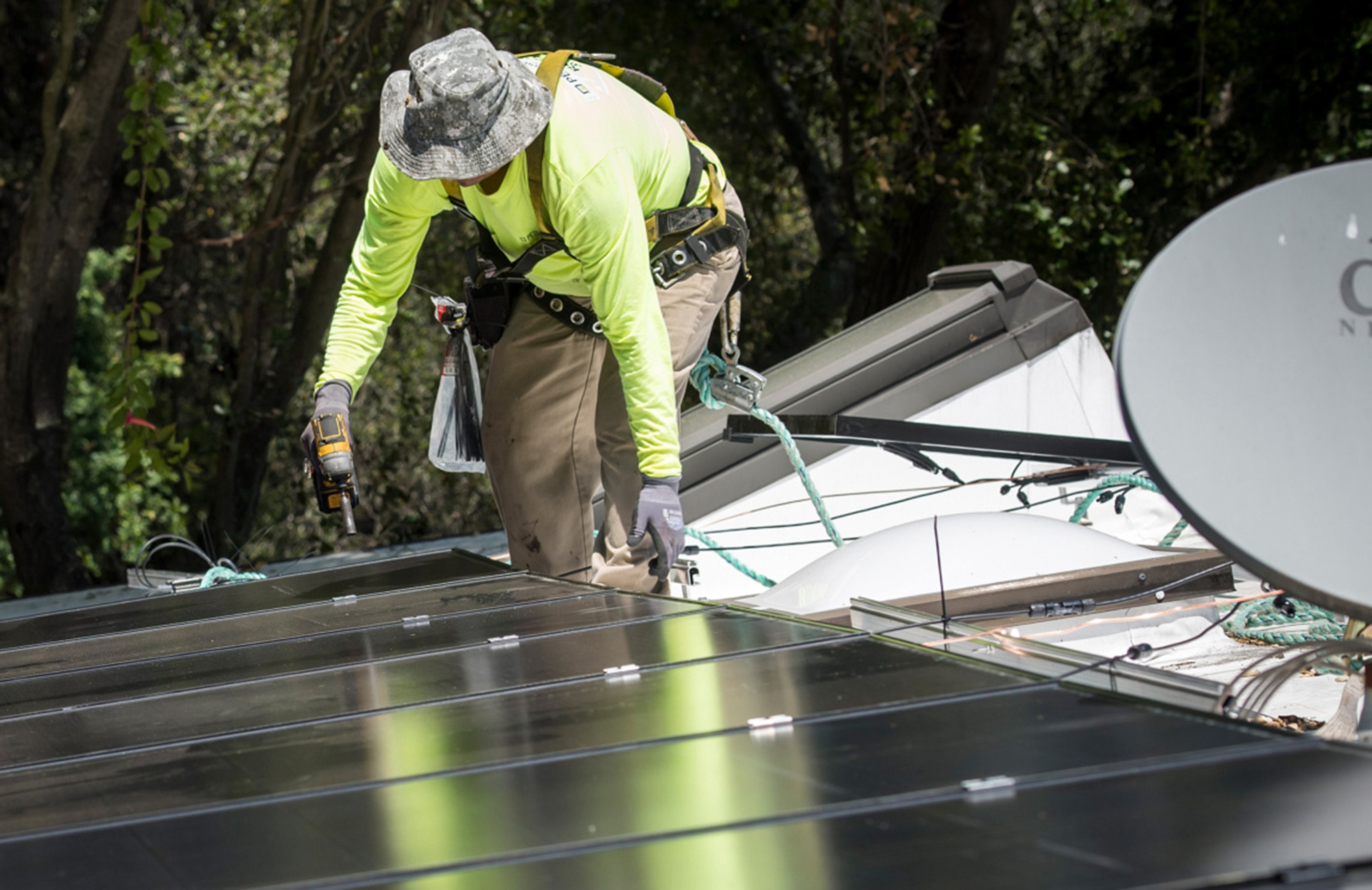 A worker installs solar panels on the roof of a home in California.