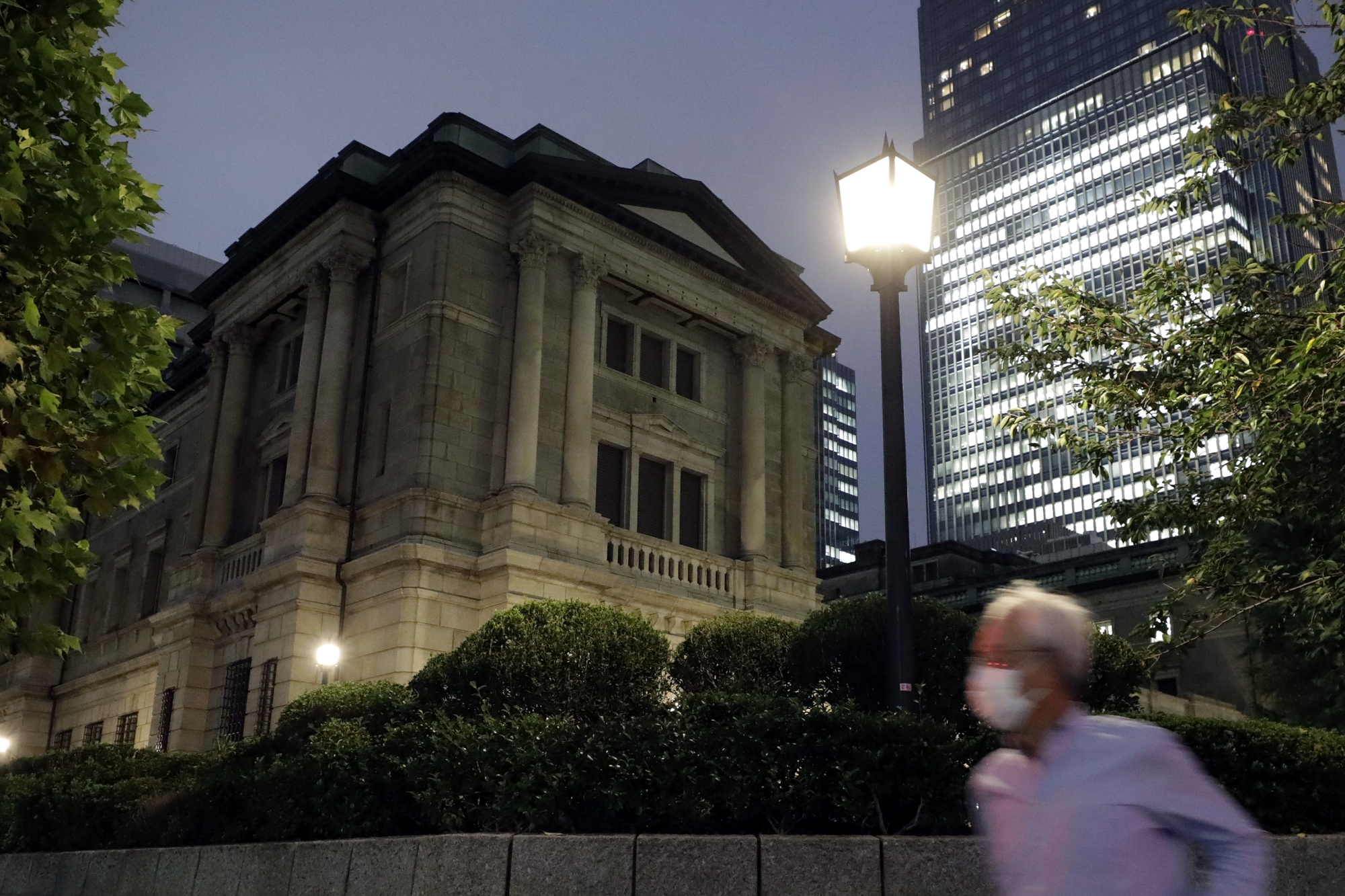 A pedestrian wearing a protective mask passes by the Bank of Japan (BOJ) headquarters at dusk in Tokyo, Japan.